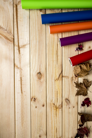 Colorful vinyl rolls on wooden background set in a row with autumn leaves