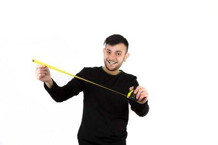 Portrait of a handsome young man holding a measuring tape isolated on white background