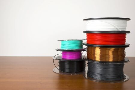3D printing filament reels isolated over white and wooden background