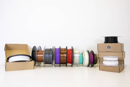 3D printing filament reels for 3d printers in boxes on white background