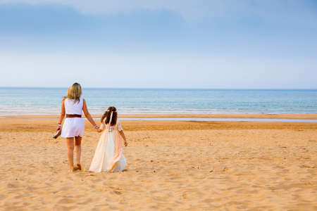 Single parent family mother and daughter lovingly holding hands walking on the sand of the beach with the sea in the background