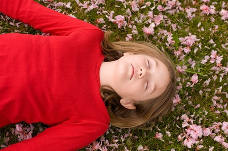 A young girl sleeping in a bed of apple blossoms Stok Fotoğraf