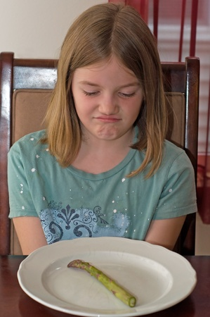 young girl with a disgusted facial expression over vegetables photo