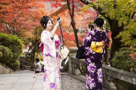 Beautiful Young Japanese Women on Kimono take a photo in Kiyomizudera, Kyoto, Japan, November 22, 2012