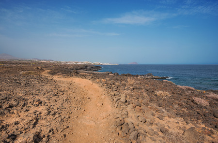 Path in scenic volcanic landscape bordered by coastline in south Tenerife island, Canary islands, Spain. Stock Photo