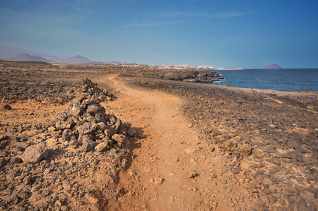 bordered: Path in scenic volcanic landscape bordered by coastline in south Tenerife island, Canary islands, Spain. Stock Photo