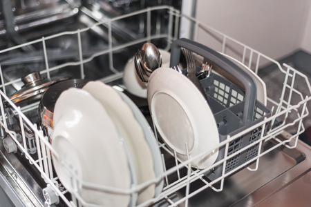 lavar platos: Open dishwasher with clean glass and dishes, selective focus