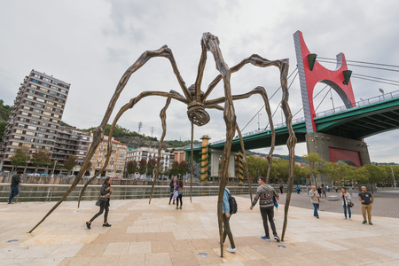 Bilbao, Spain - October 16: Group of tourist visiting Louise Bourgeois giant 11 meter high spider at the back of the Guggenheim museum on October 16, 2016 in Bilbao, Spain.