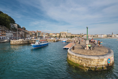 San Sebastian, Spain - June 10, 2017: Boats docked and people walking in marina of San Sebastian harbor, Basque country, Spain.