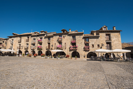Ainsa, Spain - October 9, 2017: Tourist visiting main square of Ainsa. Is a medieval village of stone houses in Aragonese pyrenees, Huesca, Span.