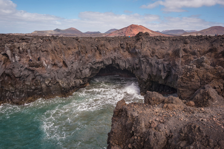 Lanzarote landscape. Los Hervideros coastline, lava caves, cliffs and wavy ocean. Unidentifiable tourist are in the background 스톡 콘텐츠