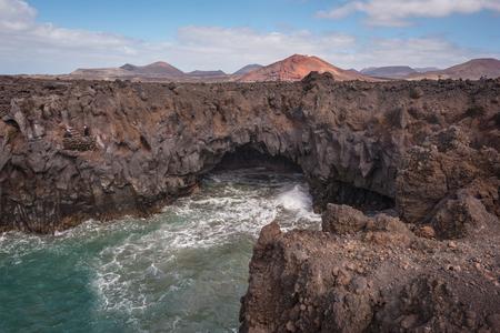 Lanzarote landscape. Los Hervideros coastline, lava caves, cliffs and wavy ocean. Unidentifiable tourist are in the background Stock Photo