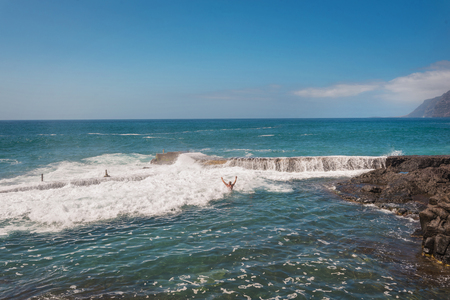 Unidentifiable Tourist swimming in coastline landscape in Puerto Santiago, Tenerife, Spain. 스톡 콘텐츠