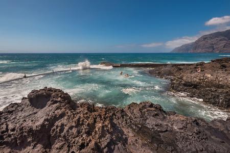 Unidentifiable Tourist swimming in coastline landscape in Puerto Santiago, Tenerife, Spain. Stock Photo