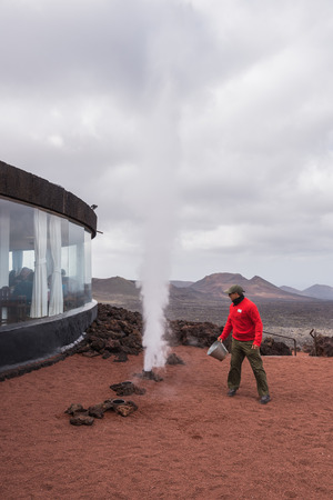 Lanzarote, Spain - February 12, 2018: Artificial volcanic geyser demonstration in Timanfaya volcanic national park in Lanzarote, Canary islands, Spain.