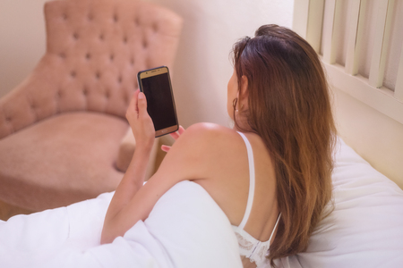 Young woman holding a mobile phone while lying on bed. Stock Photo