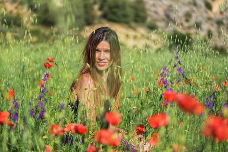 Woman enjoying a walk in a poppy field under the summer sun.