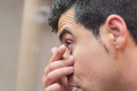 Young man putting contact lens in his eye