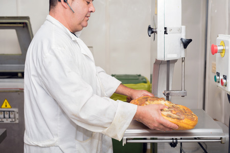Close up of worker hands in the industrial process of cutting iberian ham