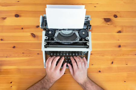 Writer's hands. Old retro typewriter on wooden desk.