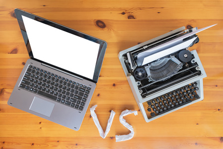 Old typewriter vs new laptop on the table. Concept of technology progress.