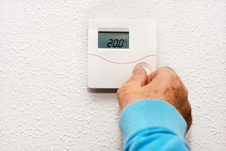 Man hand adjusting thermostat at home. Celsius temperature scale.