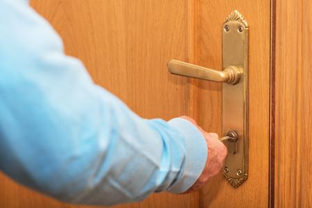 Senior man Locking up door with key in hand