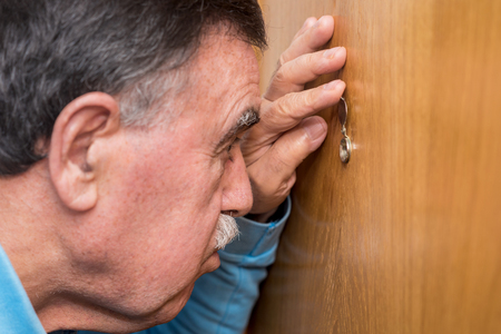 Senior man looking through peephole Stock Photo
