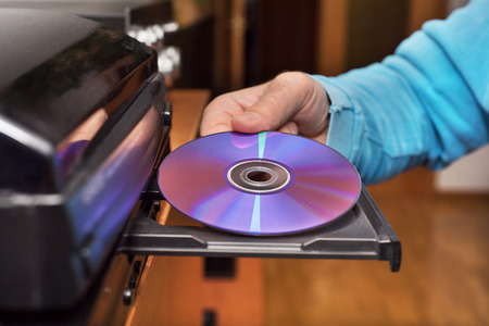Hand holding DVD inserting to video player Stock Photo