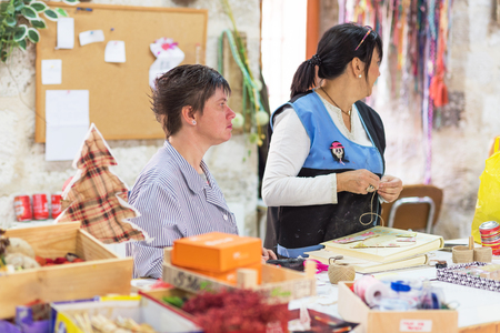 Briviesca, Spanje - 7 november 2018: Mensen met speciale behoeften of een handicap die met hun leraren werken in de werkplaats van ergotherapie Redactioneel