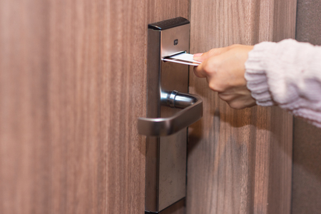 Woman hand inserting card to open electronic lock in hotel door Stockfoto
