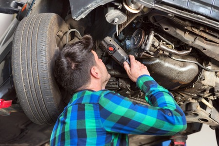 Handsome car mechanic checking suspension system of a lifted car at repair service station.