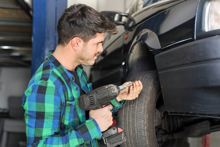 Mecanic checking car suspension system, at repair service station.
