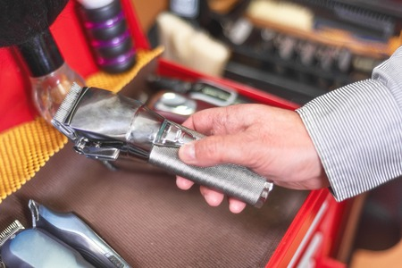 Close up of barber hand picking hair clipper at barber shop. Banque d'images