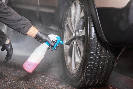 Professional car washer cleaning alloy wheels.