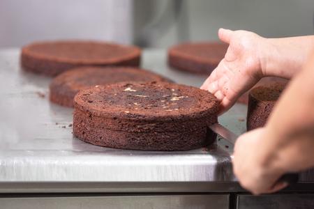 Professioneller Konditor, der in der Konditorei einen köstlichen Kuchen macht.