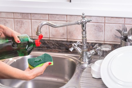 woman with red manicure putting detergent in the scourer, to wash the dishes.