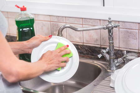 Young woman with red manicure, washing dishes in the sink of the kitchen.