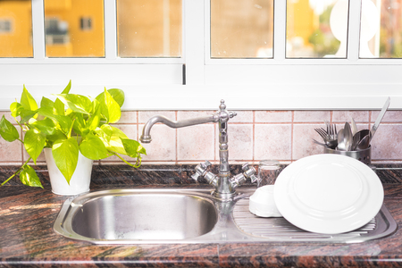 The Clean dishes are drying, on rustic kitchen metal sink.