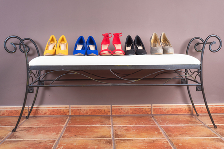 Collection of woman high heel shoes, on white sofa .