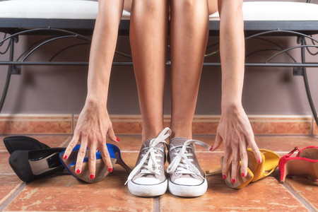 Woman with perfect slim legs, choosing comfortable sneakers rather than uncomfortable high heels shoes.