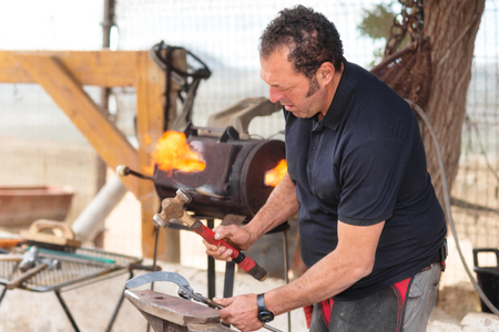 Blacksmith working on the anvil, making a horseshoe.