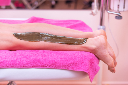 Beautician waxing woman legs, depilation in beauty Spa.