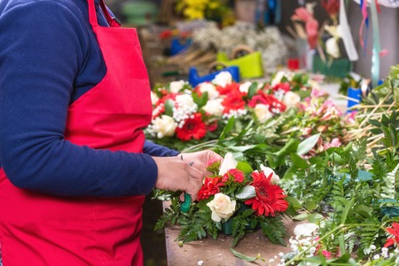 Close up of female florist creating beautiful bouquet at flower shop.