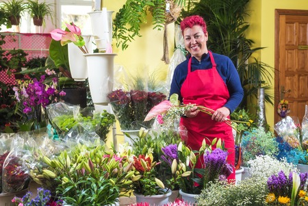 Happy woman florist, making arrangements, and smiling at camera. small business Flower shop owner.