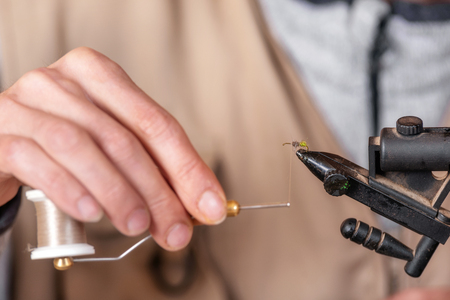 Close up of fisherman tying a fly for fishing.