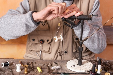 Man making trout flies. Fly tying equipment and material for fly fishing preparation.