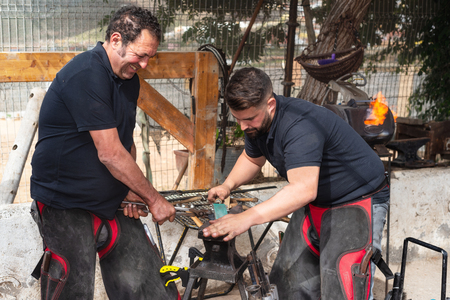 Blacksmith team working on the anvil, making a horseshoe.