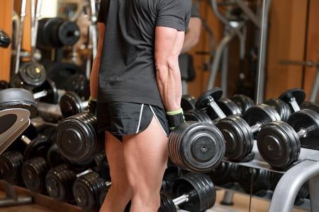 Nahaufnahme eines nicht identifizierbaren muskulösen Mannes, der schwere Hantelgewichte vom Geräteständer im modernen Fitnessstudio aufhebt.