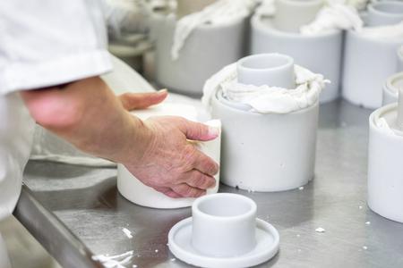 Mujer trabajadora preparando masa cruda de queso en moldes